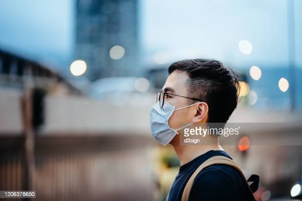 portrait of young asian man with face mask to protect and prevent from the spread of viruses in the city - mondmasker stockfoto's en -beelden