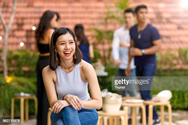 portrait of young asian woman at outdoor roof top party with friends - malaysian culture stock pictures, royalty-free photos & images