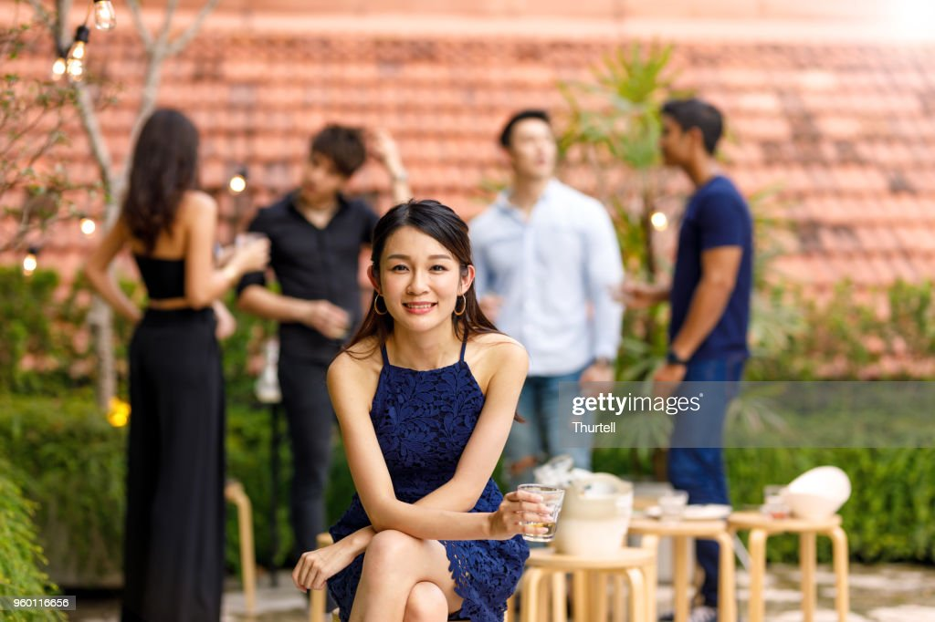 Portrait Of Young Asian Woman At Outdoor Roof Top Party With Friends : Stock Photo
