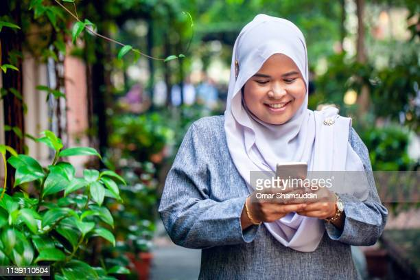 portrait of young asian woman in hijab with smart phone on street in the city - omar shamsuddin stock pictures, royalty-free photos & images