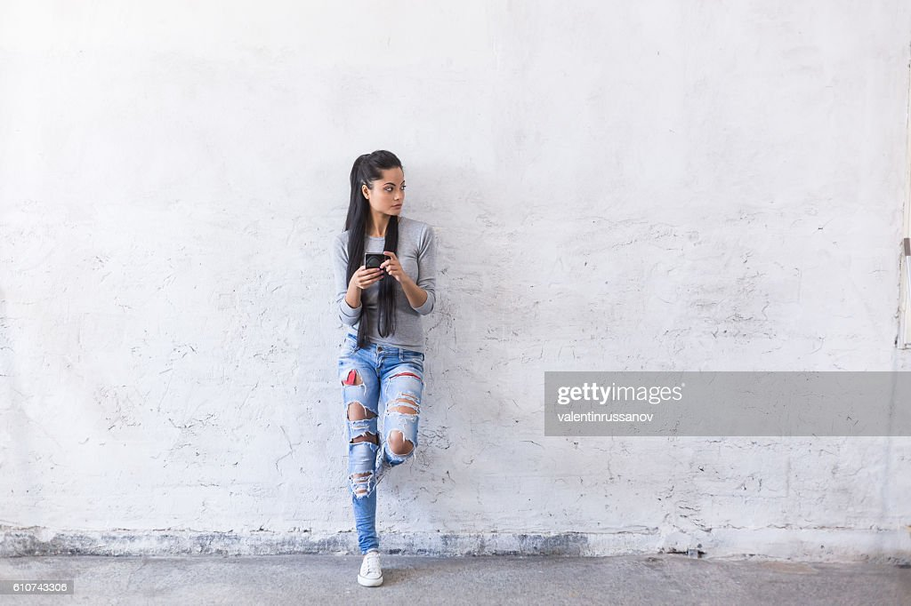 Portrait of young asian woman leaning back on blank wall : Stock Photo