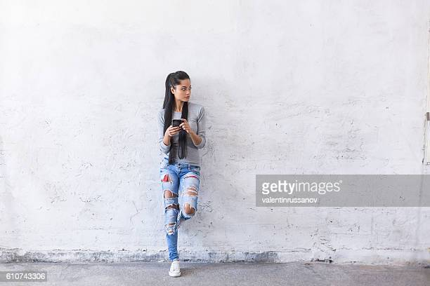 portrait of young asian woman leaning back on blank wall - jeans stock photos and pictures