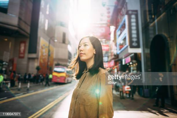 portrait of young asian woman looking up into the sky against busy urban street - far east stock photos and pictures
