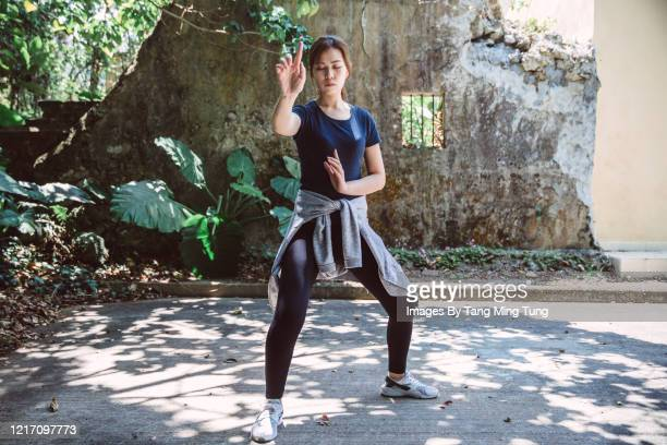 portrait of young asian woman practicing kung fu in rural area - martial arts stock pictures, royalty-free photos & images