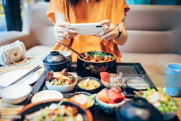 portrait of young asian woman taking picture of her fresh japanese food with mobile phone in restaurant. - etnia foto e immagini stock