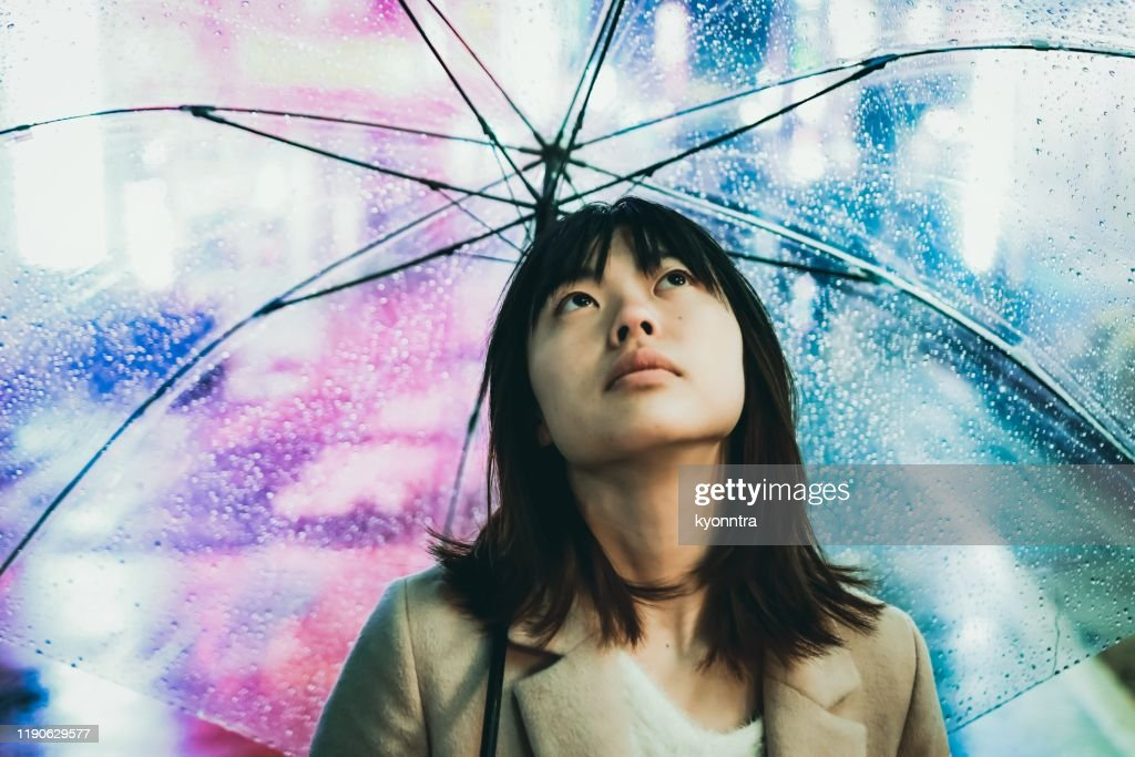 Portrait of young asian woman under raining in the night city : Stock Photo