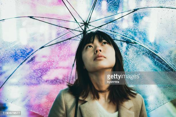 portrait of young asian woman under raining in the night city - kyonntra stock pictures, royalty-free photos & images