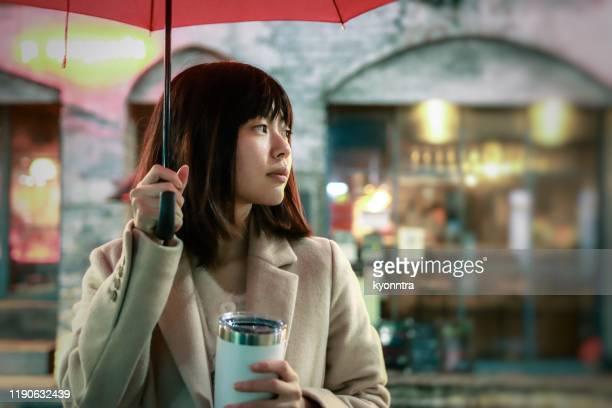夜の街で雨が降っている若いアジアの女性の肖像 - 待つ ストックフォトと画像