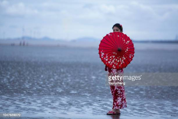 portrait of young asian woman wearing kimono with red umbrella,walking on beach - kimono stock pictures, royalty-free photos & images