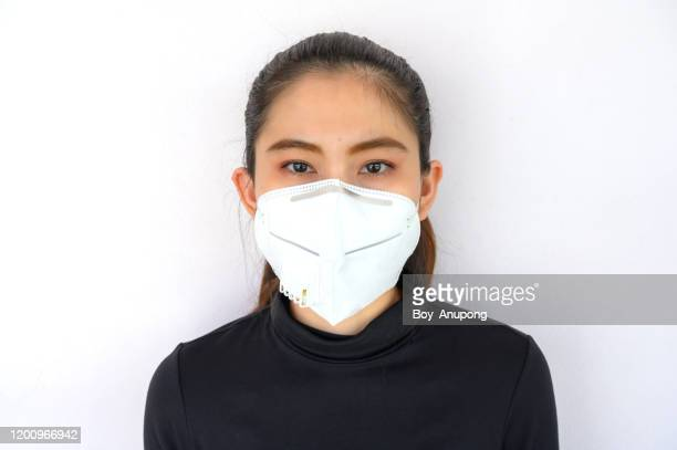 portrait of young asian woman wearing n95 mask for protect smog pm2.5 bad air pollution. - nose mask stock pictures, royalty-free photos & images