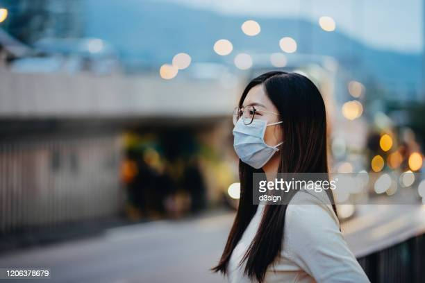 portrait of young asian woman with face mask to protect and prevent from the spread of viruses in the city - coronavirus stock pictures, royalty-free photos & images