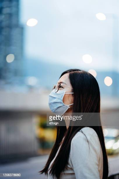 portrait of young asian woman with face mask to protect and prevent from the spread of viruses in the city - epidemia fotografías e imágenes de stock