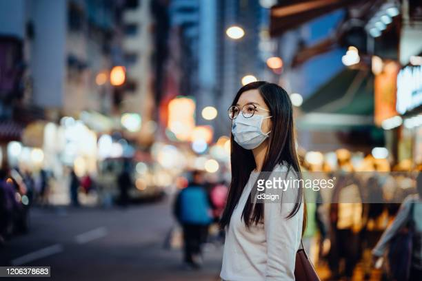 portrait of young asian woman with face mask to protect and prevent from the spread of viruses in the city - coronavirus stock-fotos und bilder