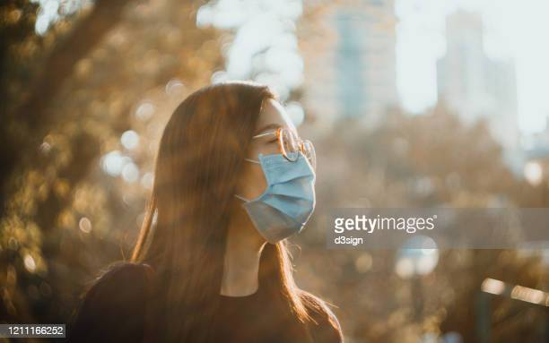 portrait of young asian woman with face mask to protect and prevent from the spread of viruses in the city - corona sun stock pictures, royalty-free photos & images