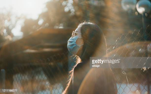 portrait of young asian woman with surgical face mask to protect and prevent from the spread of viruses in the city - hope stock pictures, royalty-free photos & images