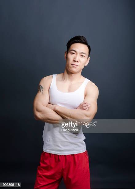 portrait of young athletic man standing against grey background - waistcoat stock photos and pictures