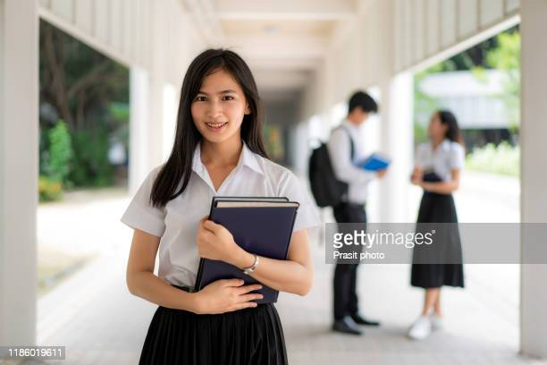 portrait of young attractive asian university student smiling and looking at camera outdoor feeling confident and positive. headshot of thai teenager, entrepreneur or college student. - タイ人 ストックフォトと画像