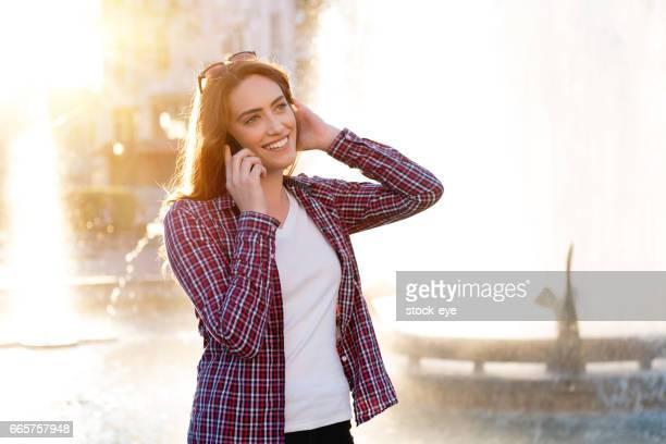 Portret van jonge aantrekkelijke student buitenkant, praten over haar telefoon