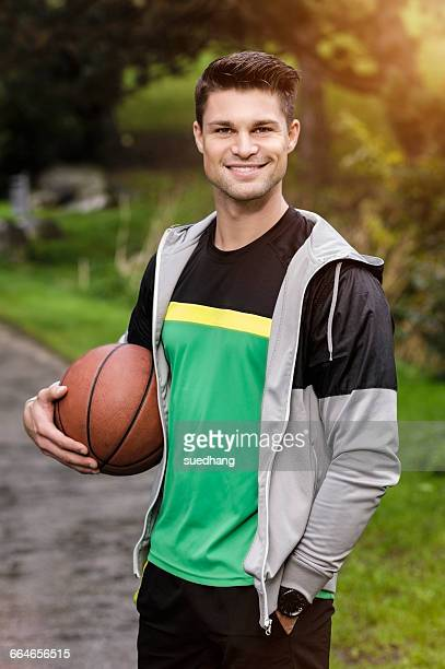 Portrait of young basketball player in park