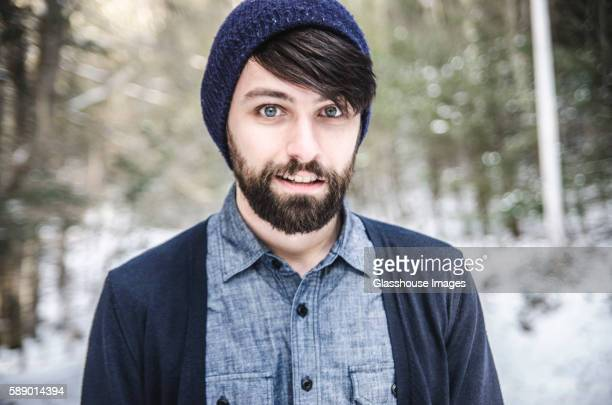 Portrait of Young Bearded Man Outside in Wool Knit Winter Hat, Chambray Shirt and Cardigan Sweater