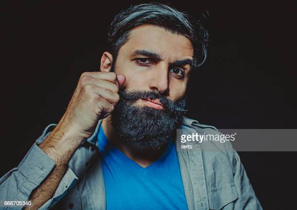 Portrait of young bearded man twisting his moustache.