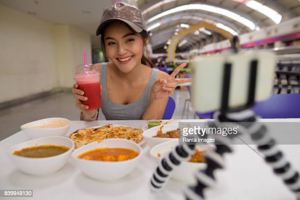 Portrait of young beautiful Asian tourist woman enjoying Indian cuisine at restaurant