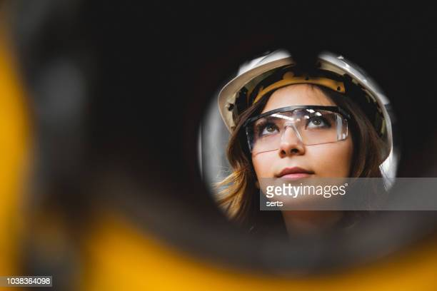 portrait of young beautiful engineer woman working in factory building. - unusual angle stock pictures, royalty-free photos & images