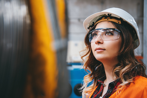 Portrait of young beautiful engineer woman working in factory building. 1038364390