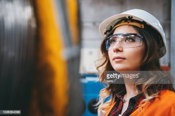 portrait of young beautiful engineer woman working in factory building. - engineering stock pictures, royalty-free photos & images