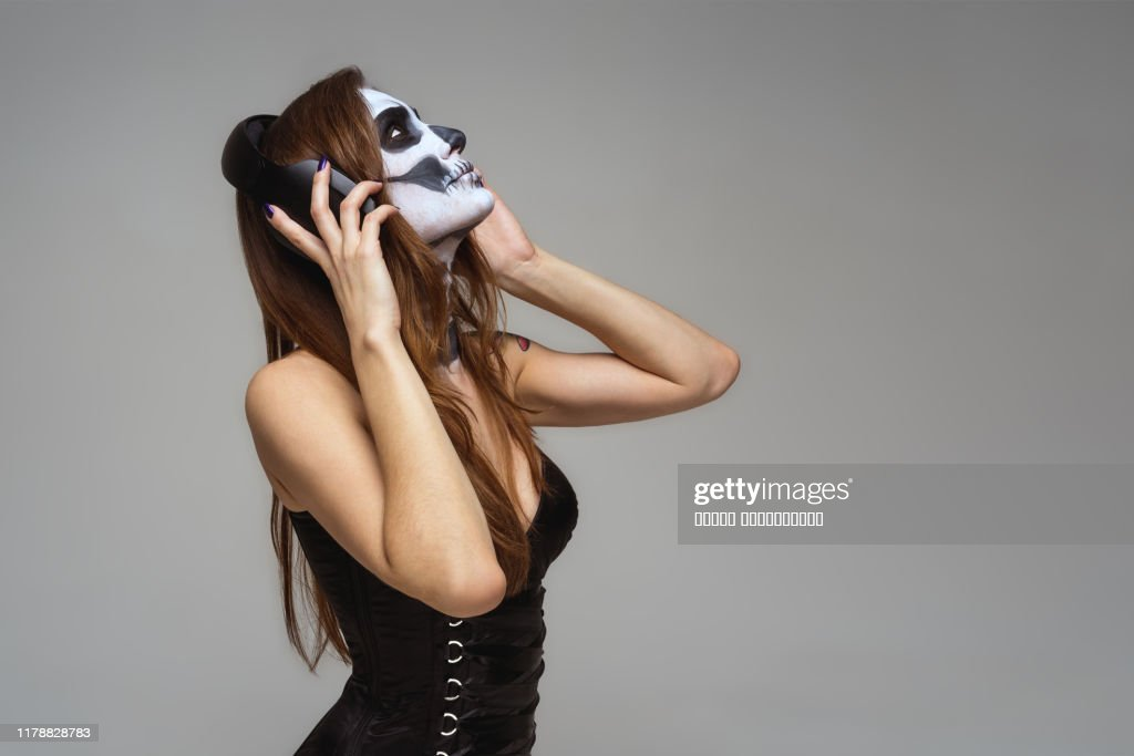 Portrait of young beautiful girl with fearful halloween skeleton makeup  Katrina Calavera in headphones listening to music on gray background : Stock Photo