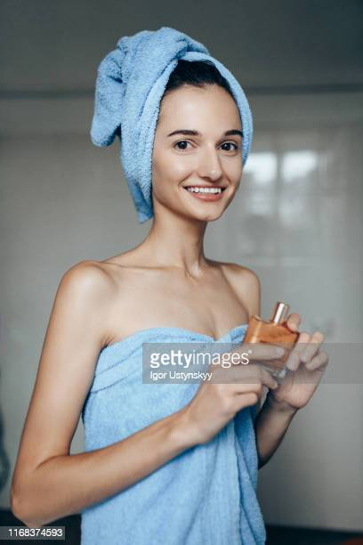 portrait of young beautiful woman holding moisturizer - no make up stock pictures, royalty-free photos & images