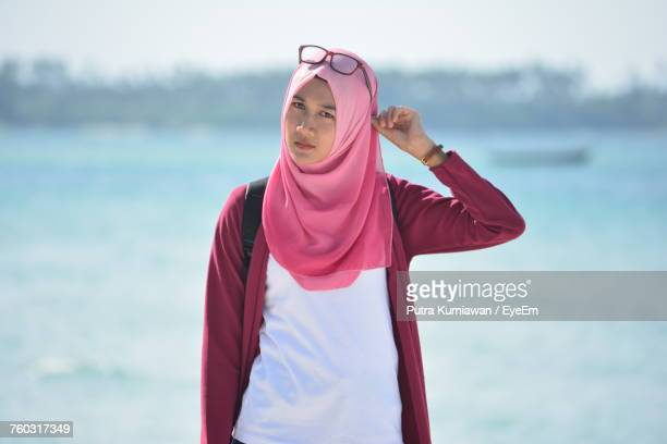 portrait of young beautiful woman wearing pink hijab standing at beach - muslim woman beach stock photos and pictures