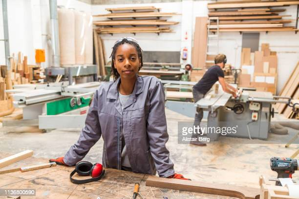 portrait of young black female worker in a furniture factory - trabalhador manual - fotografias e filmes do acervo