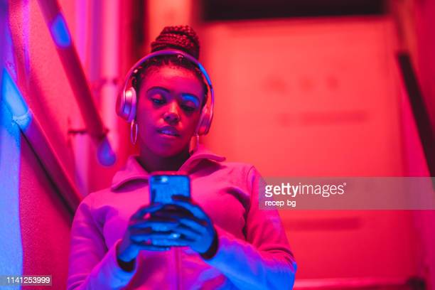 portrait of young black woman listening to music under neon lights - neon colored stock pictures, royalty-free photos & images