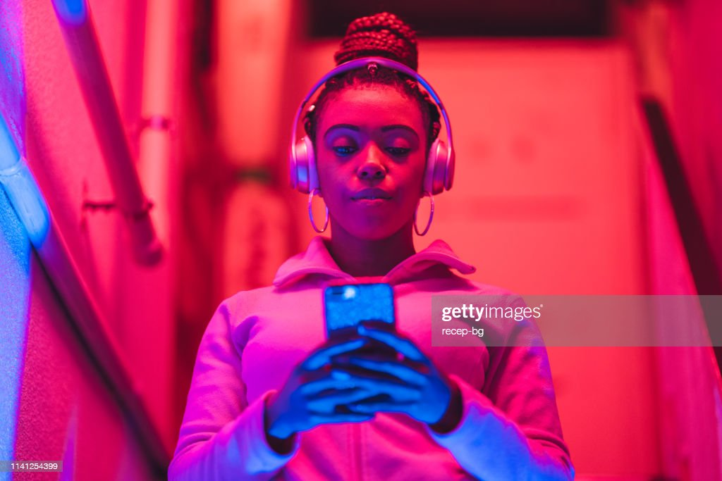 Portrait of young black woman listening to music under neon lights : Stock Photo
