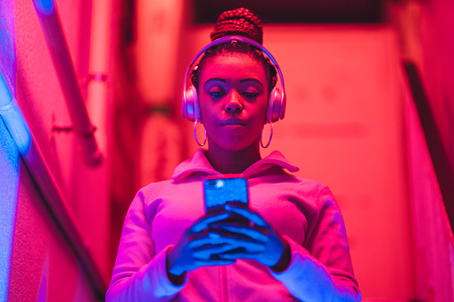 Portrait of young black woman listening to music under neon lights 1141254399