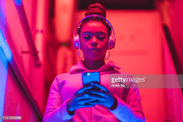 portrait of young black woman listening to music under neon lights - black blazer stock pictures, royalty-free photos & images