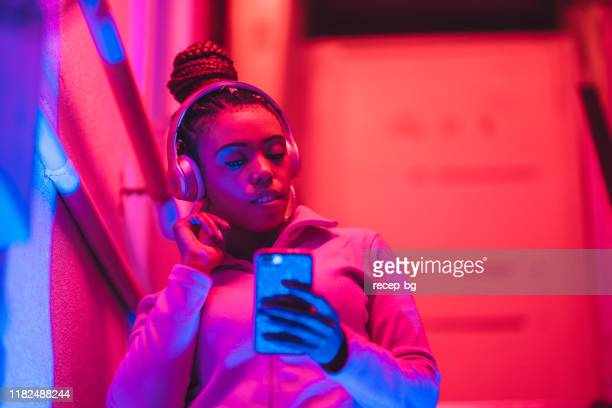 portrait of young black woman listening to music under neon lights - blue blazer stock pictures, royalty-free photos & images