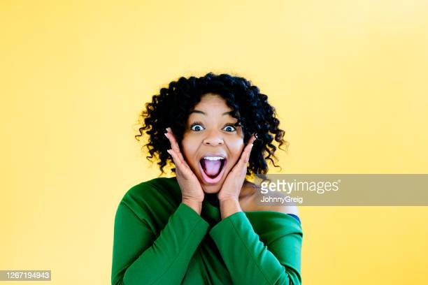 portrait of young black woman showing expression of surprise - human face stock pictures, royalty-free photos & images