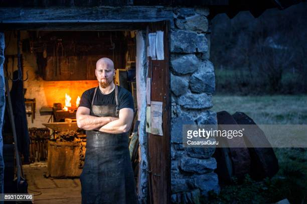 Portrait Of Young Blacksmith Standing In Front Of His Workshop