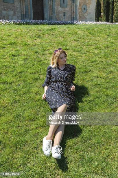 Portrait of young blond woman having rest at grassy park
