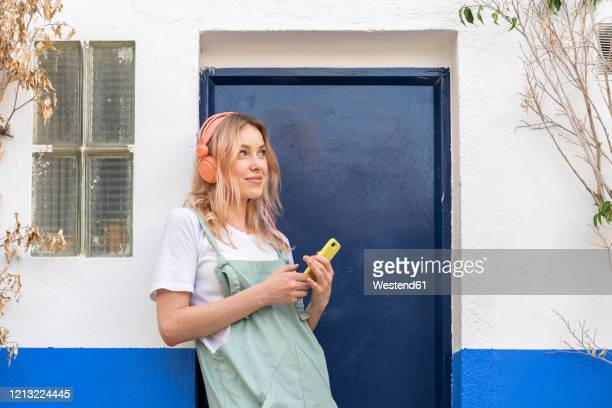 portrait of young blond woman  leaning at facade listening music with headphones and smartphone - lehnend stock-fotos und bilder