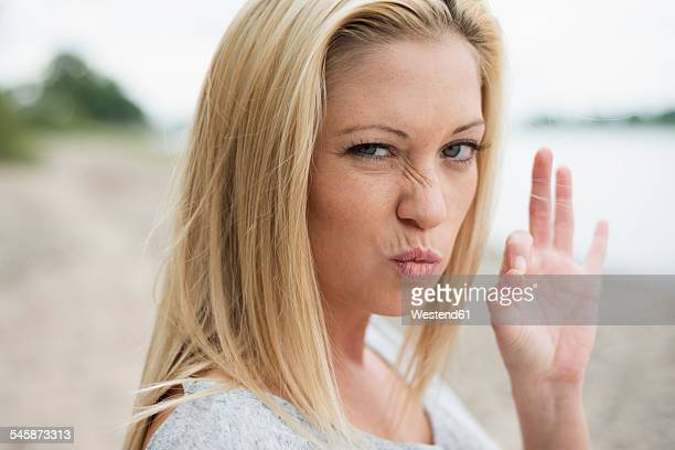 Portrait of young blond woman pouting mouth and showing ok sign