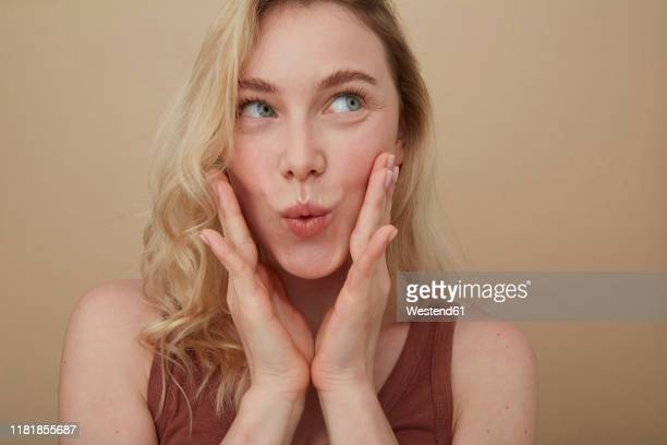 portrait of young blond woman pouting mouth - solo ragazze foto e immagini stock