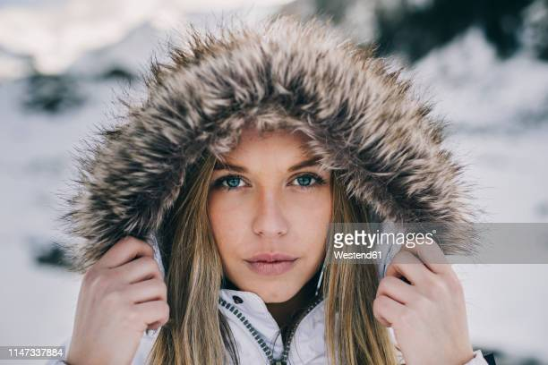 portrait of young blond woman wearing hood in winter - winter coat stock pictures, royalty-free photos & images