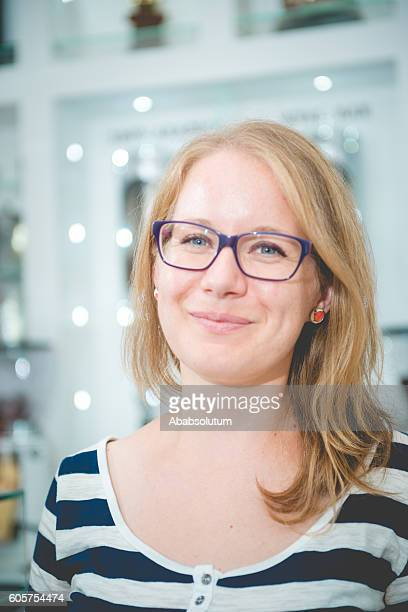Portrait of Young Blond Woman with Eyeglasses in Cafe, Slovenia