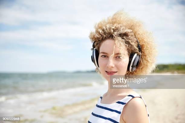 portrait of young blond woman with headphones on the beach - schleswig holstein stock-fotos und bilder