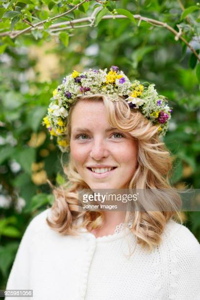 portrait of young blonde smiling woman with flower wreath on head - summer solstice stock pictures, royalty-free photos & images