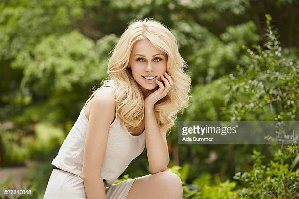Portrait of young blonde woman in park