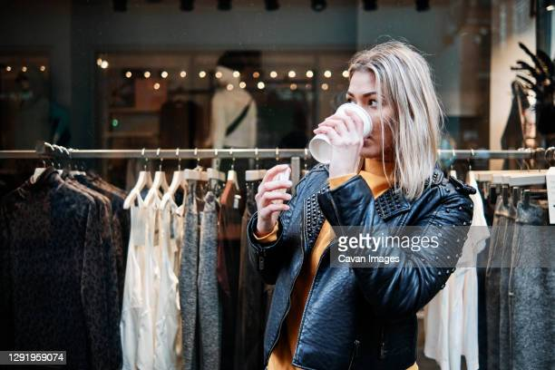 portrait of young blonde woman wearing black leather jacket, drinking cup of coffee during shopping n front of shopping window with clothes behind. - city life stock pictures, royalty-free photos & images